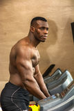 Muscular black male bodybuilder exercising on treadmill in gym Royalty Free Stock Photography