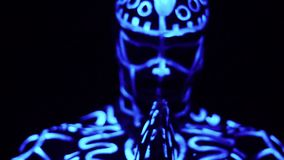 A muscular black man in luminescent patterns that glows in the ultraviolet light prays in the dark and looks into the stock footage