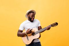 Muscular black man playing guitar, wearing jeans and white tank-top. Isolate over yellow background. royalty free stock photos