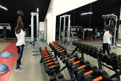 Muscular black man in a white t-shirt doing exercises with dumbbells in front of the mirror. At gym Stock Photos