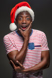 Muscular black surprised young man in Santa Claus hat Royalty Free Stock Photography
