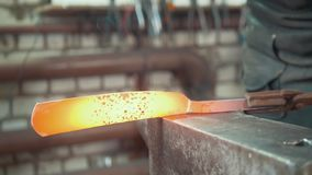 Muscular blacksmith in forge near metal anvil. Small business stock footage