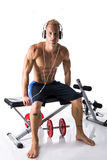Muscular blond young man lifting weights and listening to music in headphones Royalty Free Stock Photography