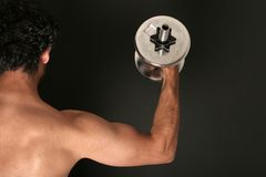 Muscular body builder. Man working out with dumbbell royalty free stock photo