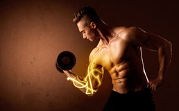 Muscular body builder lifting weight with energy lights on bicep Royalty Free Stock Photos