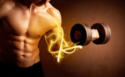 Muscular body builder lifting weight with energy lights on bicep Royalty Free Stock Images