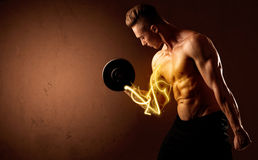 Muscular body builder lifting weight with energy lights on bicep Royalty Free Stock Image
