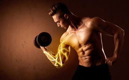 Muscular body builder lifting weight with energy lights on bicep Royalty Free Stock Photo