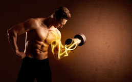 Muscular body builder lifting weight with energy lights on bicep Stock Photos