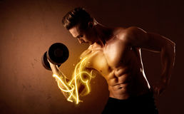 Muscular body builder lifting weight with energy lights on bicep Stock Photography