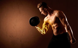 Muscular body builder lifting weight with energy lights on bicep Royalty Free Stock Photography