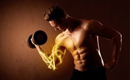 Muscular body builder lifting weight with energy lights on biceps. Concept Royalty Free Stock Images