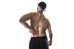 Muscular body sport man holding sore low back waist massaging with his hand suffering pain. Young muscular body sport man holding sore low back waist massaging Stock Photos