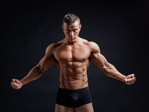 Muscular body. Young muscular bodybuilder posing over black background Stock Photos