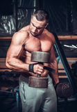 Muscular bodybuilder doing exercises with dumbbells Stock Photos
