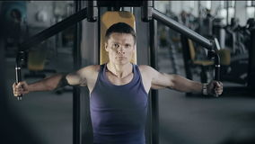 Muscular bodybuilder doing exercises workout in gym for breast muscles. Full face shot stock video