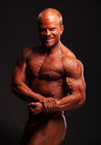 Muscular bodybuilder flexing biceps Royalty Free Stock Images