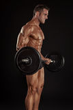 Muscular bodybuilder guy doing exercises with big dumbbell dumbb Stock Images