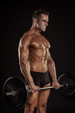 Muscular bodybuilder guy doing exercises with big dumbbell dumbb Stock Photo