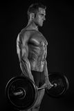 Muscular bodybuilder guy doing exercises with big dumbbell Stock Photo