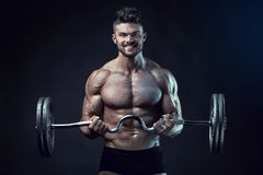 Muscular bodybuilder guy doing exercises with big dumbbell Stock Photos