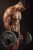 Muscular bodybuilder guy doing exercises with big dumbbell Stock Image
