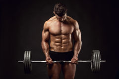 Muscular bodybuilder guy doing exercises with big dumbbell Royalty Free Stock Photos
