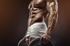 Muscular bodybuilder guy doing exercises with dumbbell disc stock image