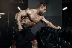 Muscular bodybuilder guy doing exercises with dumbbell in gym Stock Photo