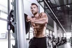 Muscular bodybuilder guy doing exercises with dumbbell on multip. Muscular bodybuilder guy doing exercises with dumbbell  on multipress in gym Royalty Free Stock Photo