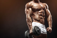 Muscular bodybuilder guy doing exercises with dumbbell. Over black background Royalty Free Stock Photo