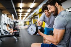 Muscular bodybuilder guy doing exercises in gym stock images