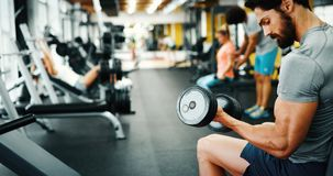 Muscular bodybuilder guy doing exercises. With dumbbells in gym Stock Photo