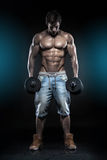 Muscular bodybuilder guy doing exercises with dumbbells over bla Royalty Free Stock Photos