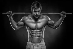 Muscular bodybuilder guy doing exercises with dumbbells over bla Royalty Free Stock Photography