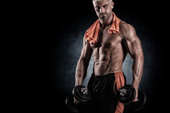 Muscular bodybuilder guy doing exercises with dumbbells over bla Royalty Free Stock Photo