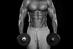 Muscular bodybuilder guy doing exercises with dumbbells. Over black background royalty free stock photography