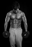 Muscular bodybuilder guy doing exercises with dumbbells. Over black background royalty free stock images
