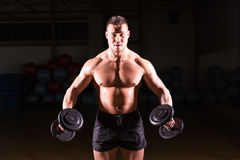 Muscular bodybuilder guy doing exercises with dumbbells. royalty free stock photos