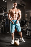 Muscular bodybuilder guy doing exercises with weight in gym Royalty Free Stock Photography