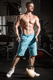 Muscular bodybuilder guy doing exercises with weight in gym Stock Photography