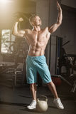 Muscular bodybuilder guy doing exercises with weight in gym Stock Photos