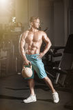 Muscular bodybuilder guy doing exercises with weight in gym Royalty Free Stock Photos