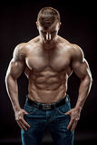Muscular bodybuilder guy doing posing over black background Royalty Free Stock Photography