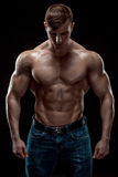 Muscular bodybuilder guy doing posing over black background Stock Images