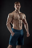Muscular bodybuilder guy doing posing over black background. Naked torso in jeans. He looks into the camera Royalty Free Stock Photo