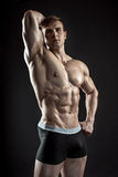 Muscular bodybuilder guy doing posing over black background Royalty Free Stock Photos