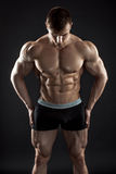 Muscular bodybuilder guy doing posing over black background. Naked torso in shorts Stock Photography
