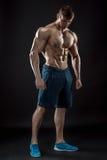 Muscular bodybuilder guy doing posing over black background. Naked torso in shorts. full height Stock Image