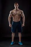 Muscular bodybuilder guy doing posing over black background. Naked torso in shorts. full height Royalty Free Stock Photo